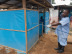 A man in Liberia disinfects the outside of an Ebola clinic. Photo by Staton Winter.