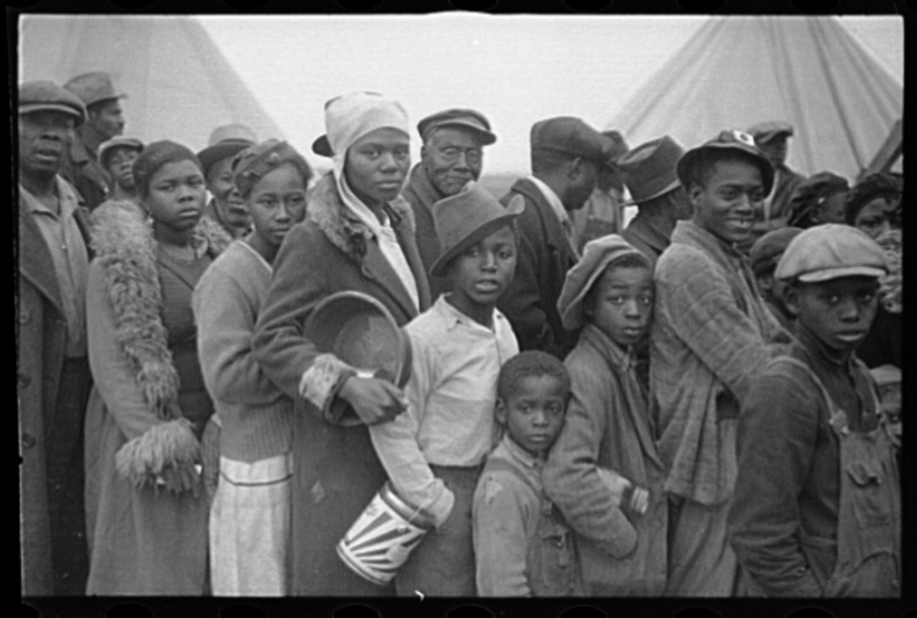 1937. Flood refugees lined up and waiting for food at Marianna, Arkansas, refugee camp. (Edwin Locke, Library of Congress)