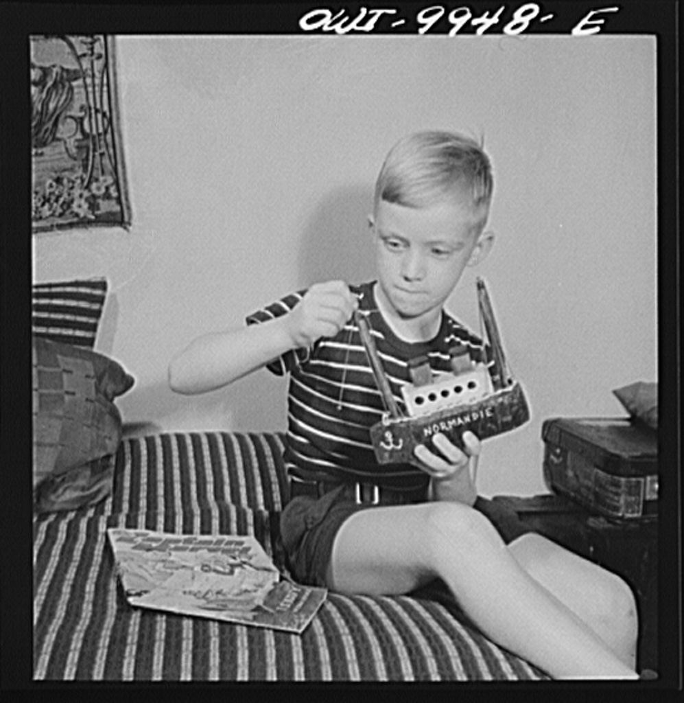 1942. New York, New York. Children's Colony, a school for refugee children administered by a Viennese. German refugee boy repairing a model of the SS Normandie which he made. (Marjory Collins, Library of Congress)