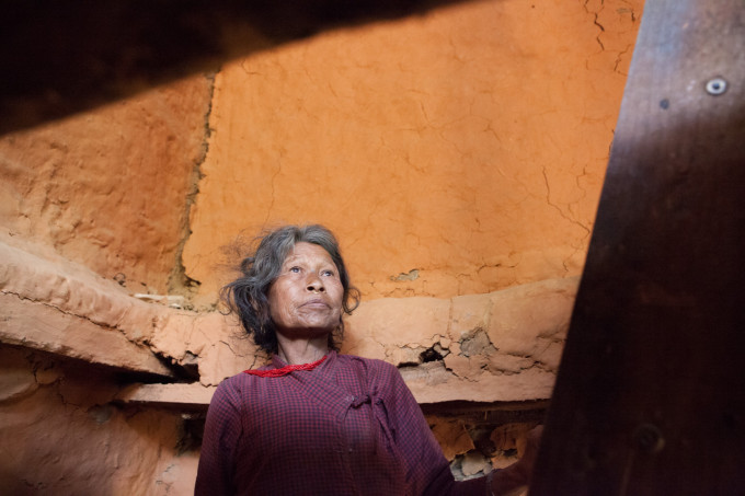 Santimai Tamang, 60, looking upstairs in her house. The house had animals in the lower room and her bedroom above.