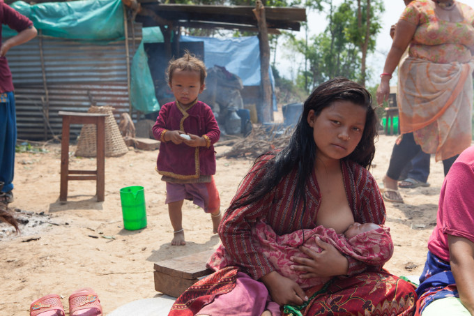 Muna Tamang and her daughter, Anusa, 1 month. They sleep together on a bed under a piece of metal sheeting.
